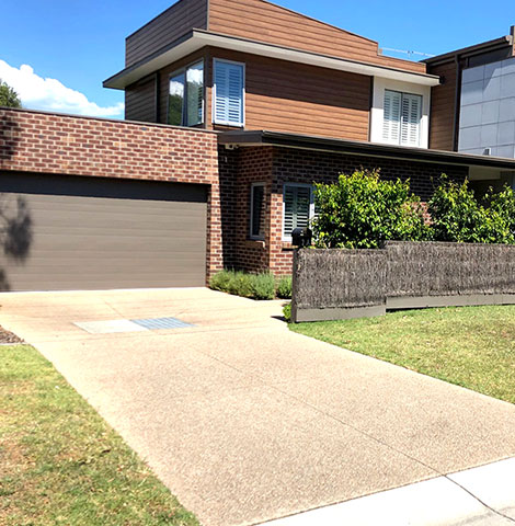 completed exposed aggregate concrete driveway with house in background